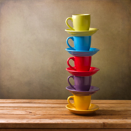Photo for Colorful coffee cups on wooden table over grunge background - Royalty Free Image