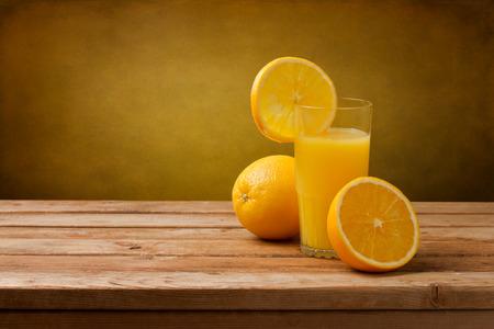 Photo for Fresh orange juice on wooden table over grunge background - Royalty Free Image