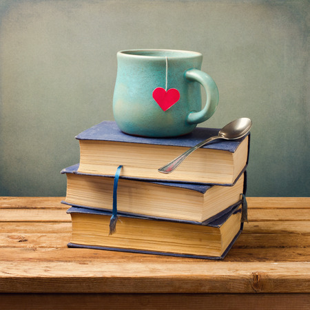 Photo for Old vintage books and cup with heart shape on wooden table - Royalty Free Image