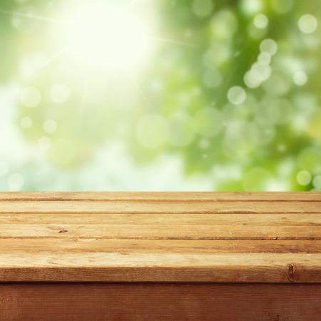 Photo pour Empty wooden deck table with foliage bokeh background. Ready for product display montage. - image libre de droit