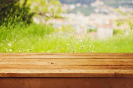 Empty wooden table over bokeh natural background