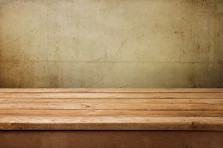 Empty wooden table over grunge concrete wall for product montage