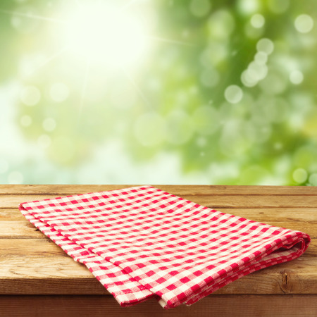 Photo pour Empty wooden deck table with tablecloth over bokeh background - image libre de droit