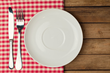Foto per Empty plate with fork and knife on tablecloth over wooden background - Immagine Royalty Free