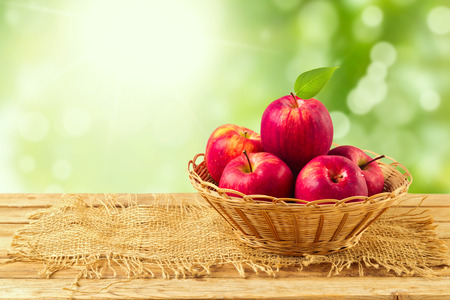 Photo for Apples in basket on wooden table over garden bokeh background - Royalty Free Image