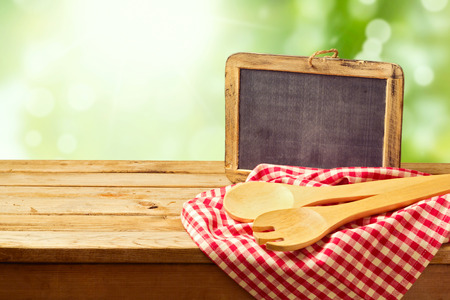 Photo pour Cooking and backing background with wooden table and chalkboard over green bokeh - image libre de droit