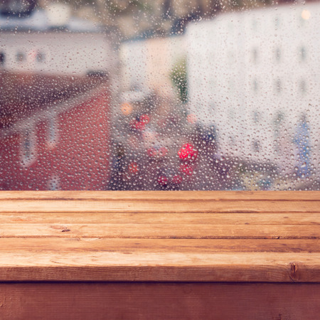 Empty wooden deck table over window with rain drops