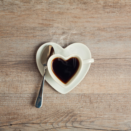 Photo pour Heart shape coffee cup on wooden table - image libre de droit