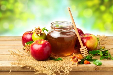 Photo pour Honey, apple and pomegranate on wooden table over bokeh background - image libre de droit