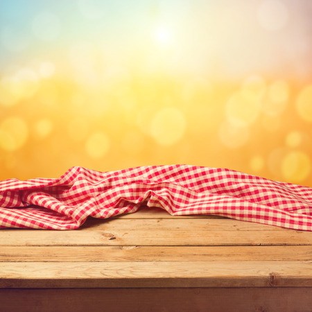 Photo pour Empty wooden deck table with tablecloth sunset bokeh background - image libre de droit