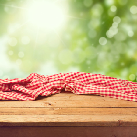 Photo pour Empty wooden deck table with tablecloth over green bokeh background - image libre de droit