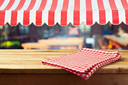 Foto de Retro wooden counter with tablecloth and awing for product montage display - Imagen libre de derechos