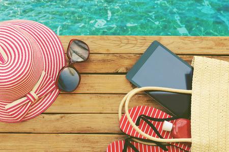 Foto de Summer holiday bag with tablet and flip flops on wooden deck. View from above - Imagen libre de derechos