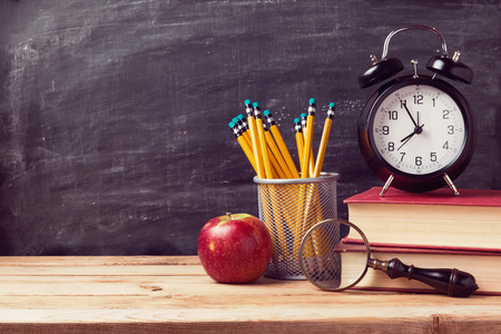 Foto de Back to school background with books and alarm clock over chalkboard - Imagen libre de derechos