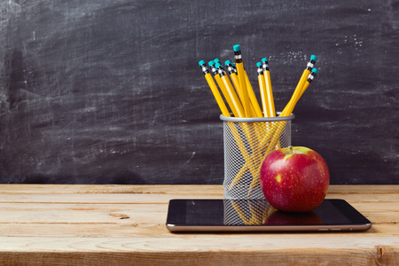 Photo pour Back to school background with tablet, pencils and apple over chalkboard - image libre de droit