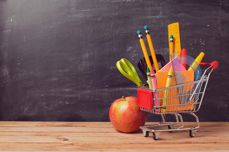 Foto de Shopping cart with school supplies over chalkboard background - Imagen libre de derechos