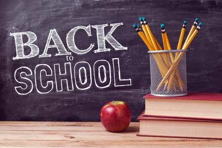 Photo pour Back to school lettering with books, pencils and apple over chalkboard background - image libre de droit