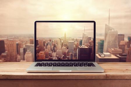 Foto de Laptop computer over New York city skyline. Retro filter effect - Imagen libre de derechos
