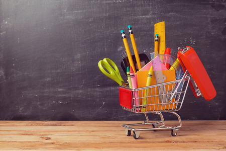 Foto de Shopping cart with school supplies over chalkboard background. Back to school sale concept - Imagen libre de derechos