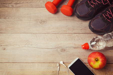Photo pour Fitness background with bottle of water, dumbbells and athletic shoes. View from above - image libre de droit