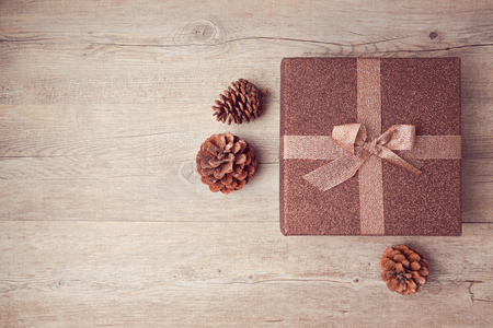 Photo for Christmas gift box with pine corn on wooden background. View from above - Royalty Free Image