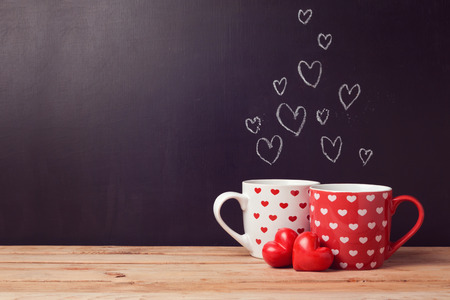 Photo pour Valentine's day concept with hearts and cups over chalkboard background - image libre de droit