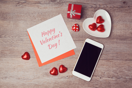 Photo pour Valentine's day flat lay with note paper and smartphone. View from above - image libre de droit