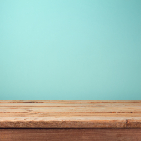 Empty wooden deck table over mint wallpaper background