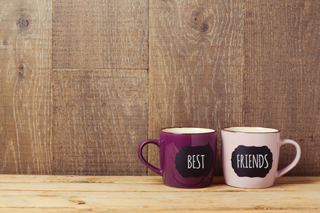 Photo for Coffee cups on wooden table with chalkboard sign and best friends text. Friendship day celebration background - Royalty Free Image