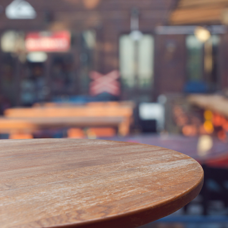 Empty wooden round table over outdoor restaurant background for product montage display