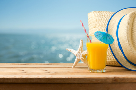 Foto de Summer holiday vacation concept with orange juice, hat and bag over sea beach background - Imagen libre de derechos