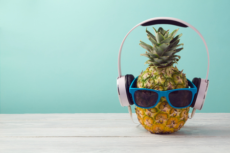 Photo pour Pineapple with headphones and sunglasses on wooden table over mint background. Tropical summer vacation and beach party concept.  - image libre de droit