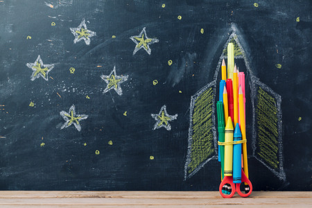 Photo pour Back to school concept with rocket made from pencils over chalkboard background - image libre de droit