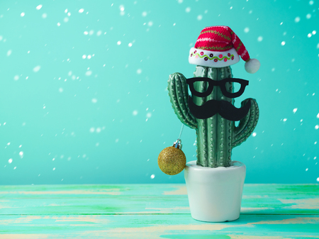 Foto de Christmas in tropical climate concept. Cactus as hipster christmas tree with santa hat - Imagen libre de derechos