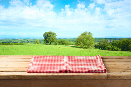 Photo pour Empty wooden table with tablecloth over summer meadow background - image libre de droit