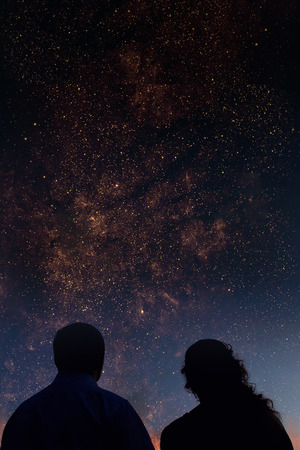 Foto de Silhouettes of couple looking at stars. Starry night sky with colorful galaxies, astronomical background with place for your text. - Imagen libre de derechos