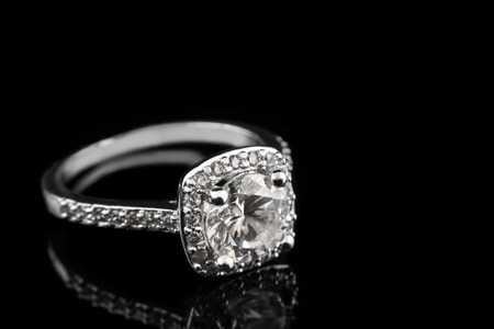Photo for Luxury jewellery. White gold or silver engagement ring with diamonds closeup on black glass background. Selective focus - Royalty Free Image