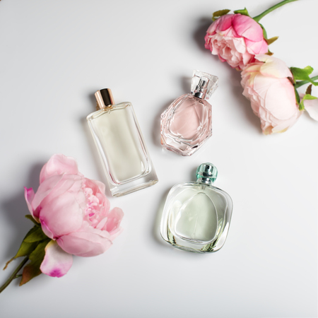 Foto de Perfume bottles with flowers on light background. Perfumery, cosmetics, fragrance collection. Flat lay - Imagen libre de derechos