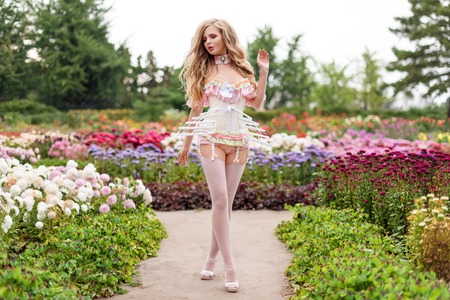 Foto de Sexy blonde woman wearing beautiful lingerie with stockings and corset, walking in blooming garden. Hot female in underware posing in sensual way outdoors. Female fashion, model fitted like a doll, barbie. - Imagen libre de derechos