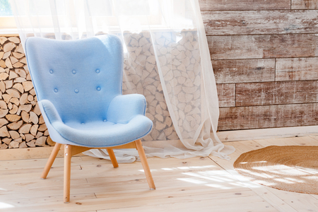 Foto de Comfortable soft armchair in scandinavian eco loft apartment. Modern minimalist living room with woodpile - Imagen libre de derechos