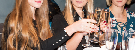 Foto de Closeup view of three female young hands holding wineglasses with champagne. Group of partying girls clinking flutes with sparkling wine. Celebration. People holding glasses making a toast - Imagen libre de derechos