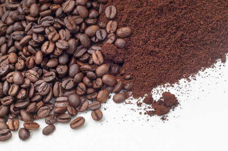 Foto de Roasted coffee beans and coffee on white surface in closeup; Coffee specialties; Processed coffee beans - Imagen libre de derechos