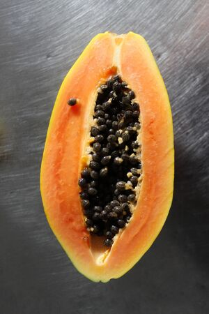Photo for Half a papaya fruit on the kitchen table. - Royalty Free Image