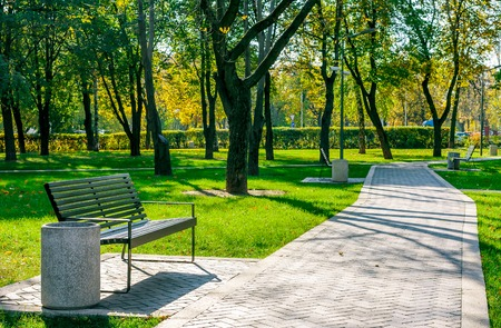 Foto de bench near the path of pavers in a quiet city park early autumn on a sunny day - Imagen libre de derechos