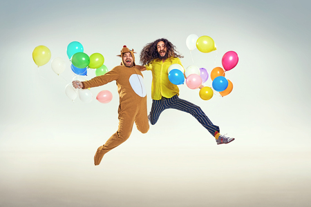 Photo pour Picture presenting two funny men jumping and holding balloons - image libre de droit