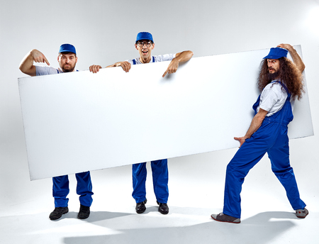 Foto de Conceptual picture of three crafstmen holding an empty, white board - Imagen libre de derechos