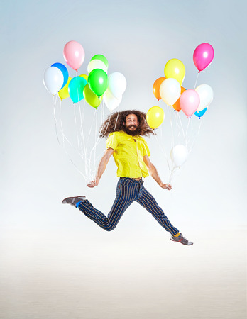 Photo for Conceptual portrait of a childish guy jumping with balloons - Royalty Free Image