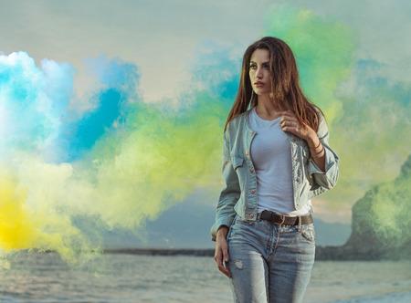Photo for Beautiful brunette lady among colorful smoke - Royalty Free Image