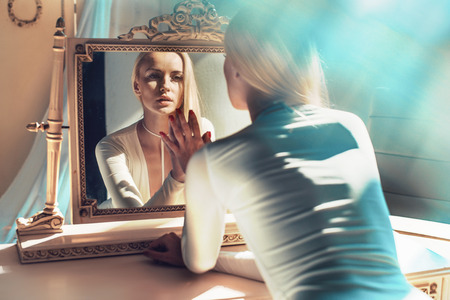 Photo for elegant blond woman looking at her mirror reflection - Royalty Free Image