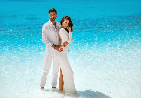Foto de Sensual, elegant couple posing on the tropical, beach - Imagen libre de derechos